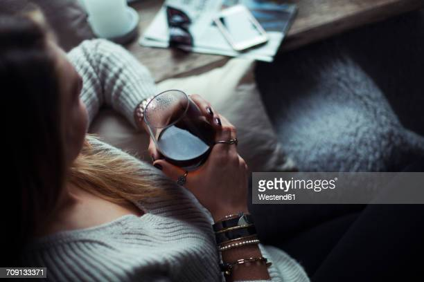 young woman with glass of coffee relaxing on couch at home - kaffee getränk stock-fotos und bilder