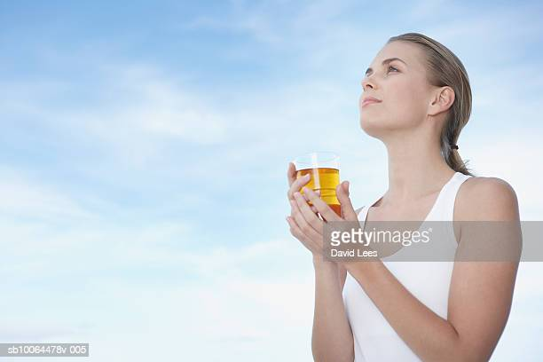 Young woman with glass of fruit juice, outdoors