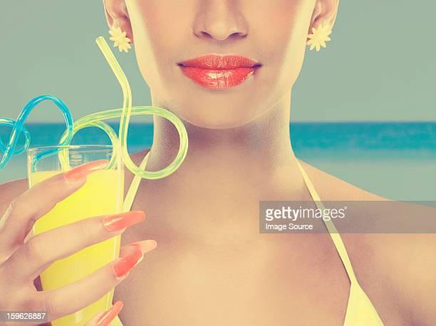 若い女性、ガラスのジュース、カーリーストロー