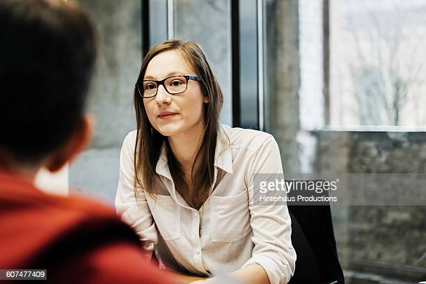 Young woman with glasses in a business meeting.