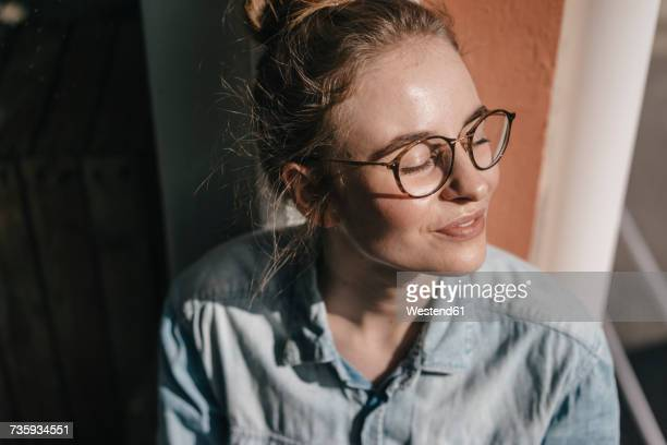young woman with glasses in sunlight - zufriedenheit stock-fotos und bilder