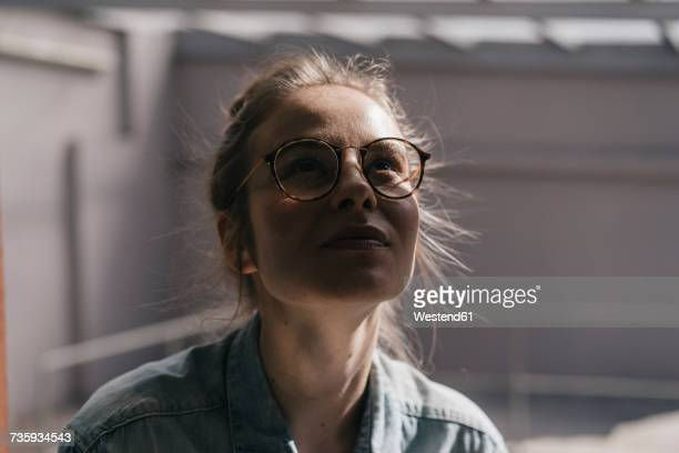 Young woman with glasses looking up