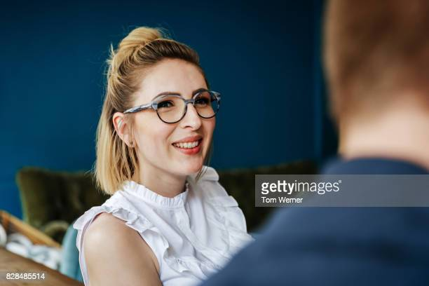 Young Woman With Glasses Talking To Friends In Cafe