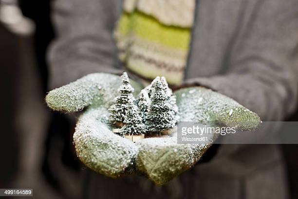 Young woman with gloves holding Christmas decoration, partial view