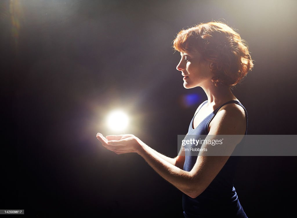 Young woman with glowing light ball. : Stock Photo