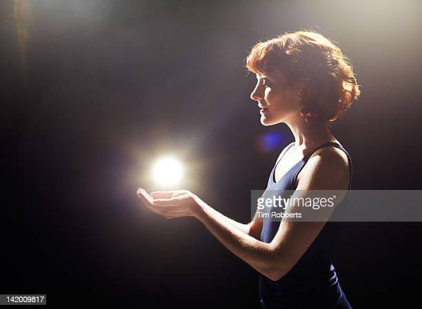 young woman with glowing light ball. - power supply stock pictures, royalty-free photos & images