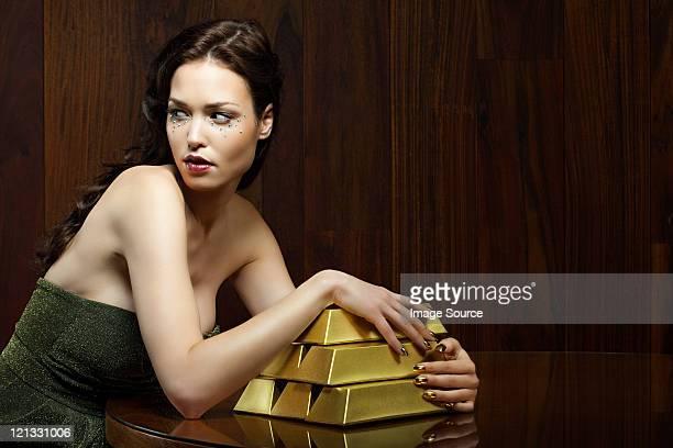 Jeune femme avec des lingots d'or