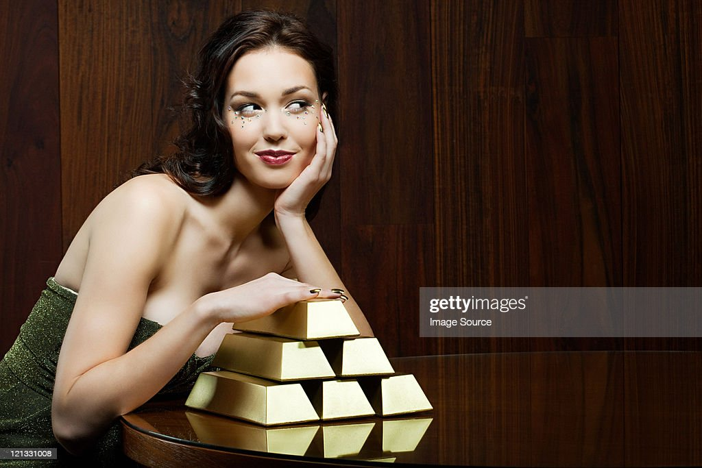 Young woman with gold ingots : Stock Photo