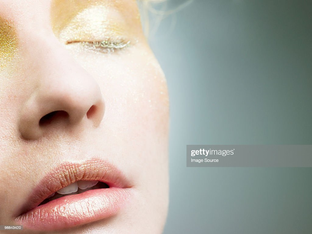 Young woman with gold make up on face : Stock Photo