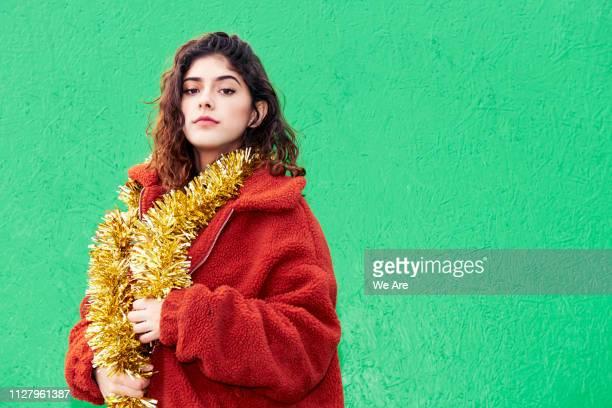 young woman with gold tinsel around shoulders - fleecejas stockfoto's en -beelden