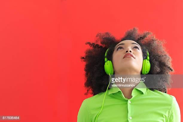 Mujer joven con auriculares verde
