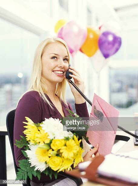Young woman with greeting card and bouquet using phone at desk