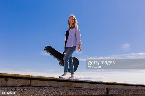 Young woman with guitar case on jetty