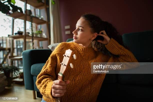 junge frau mit gitarre in ihrem wohnzimmer - musician stock-fotos und bilder