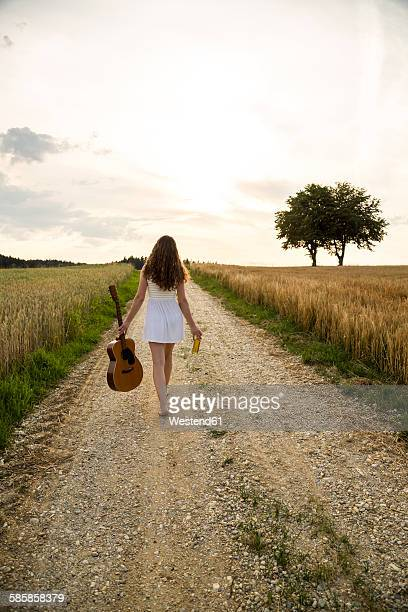 Young woman with guitar on field path, in the evening