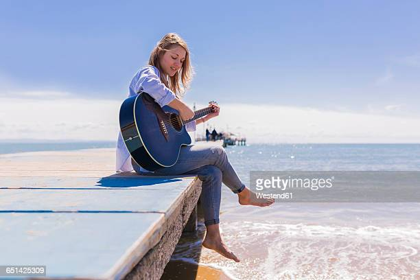 young woman with guitar sitting on jetty - classical guitar stock photos and pictures