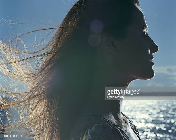 Young woman with hair blowing in wind, profile