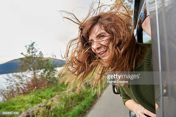 Young woman with hair blowing out car window