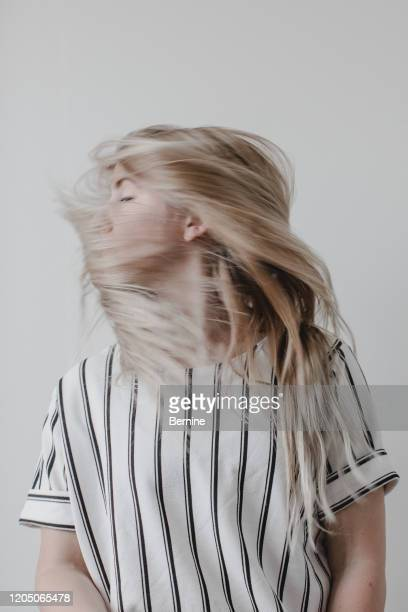 young woman with hair covering face - turning stock pictures, royalty-free photos & images
