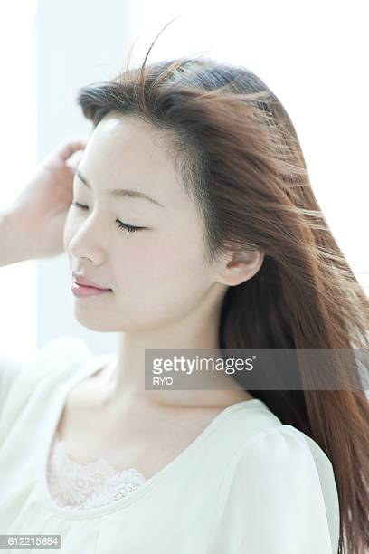young woman with hair fluttering - 髪に手をやる ストックフォトと画像