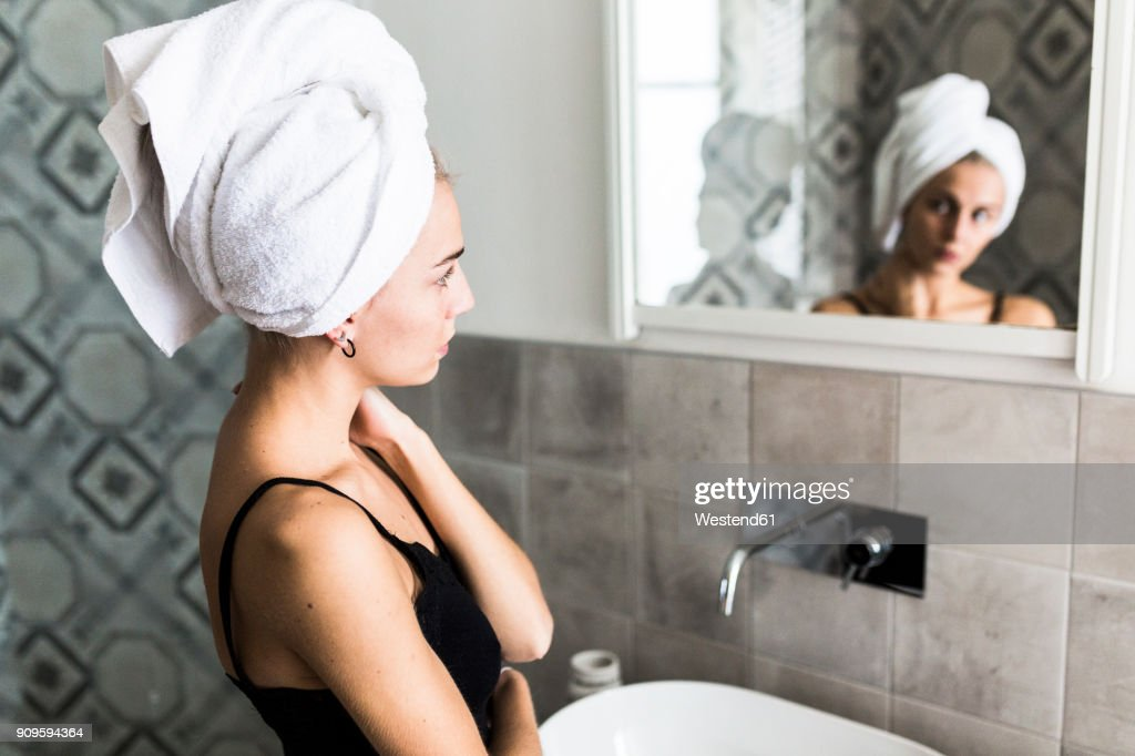 Young woman with hair wrapped in a towel looking in bathroom mirror : Stock Photo