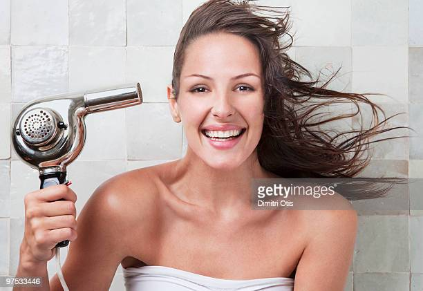 Young woman with hairdryer