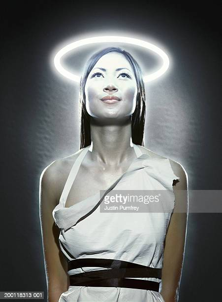 young woman with halo of flourescent light illuminating face - angel halo stock pictures, royalty-free photos & images