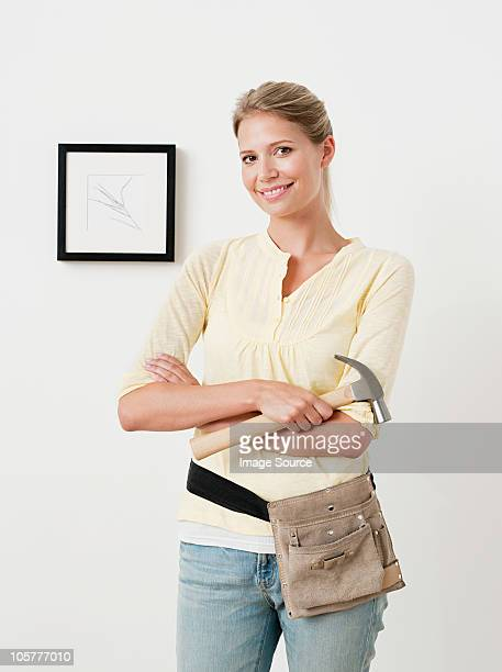 Young woman with hammer and picture on wall