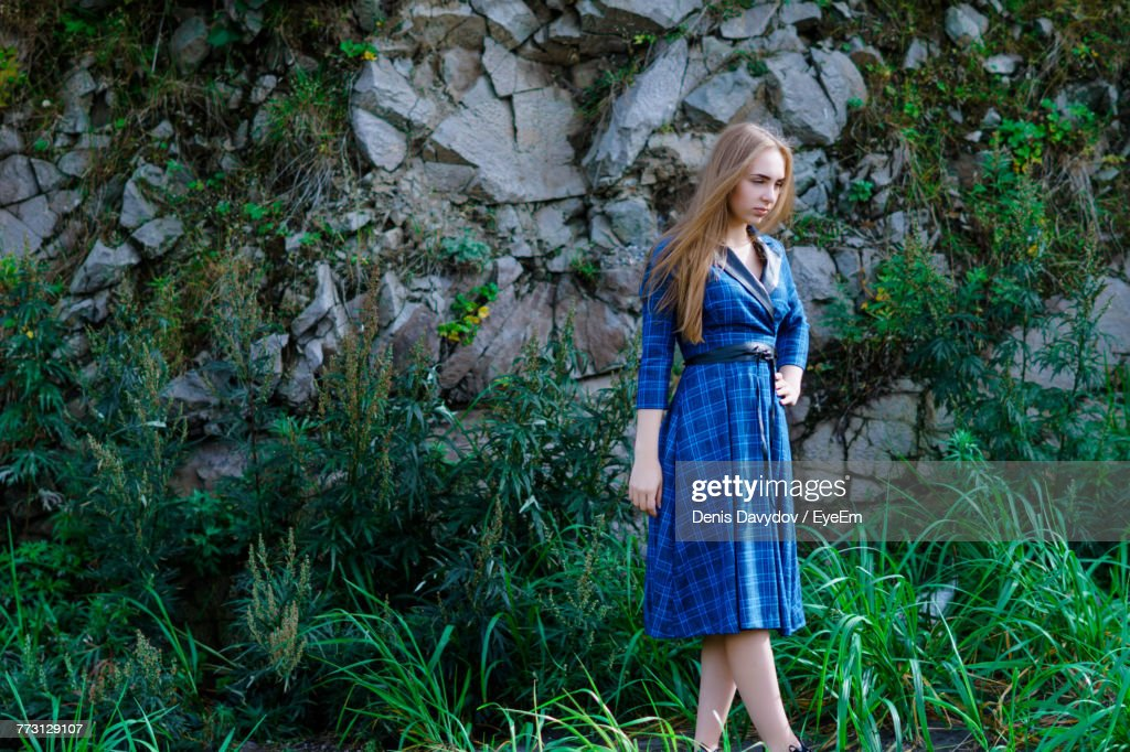 Young Woman With Hand On Hip Standing Against Rock Formation In Forest : Photo