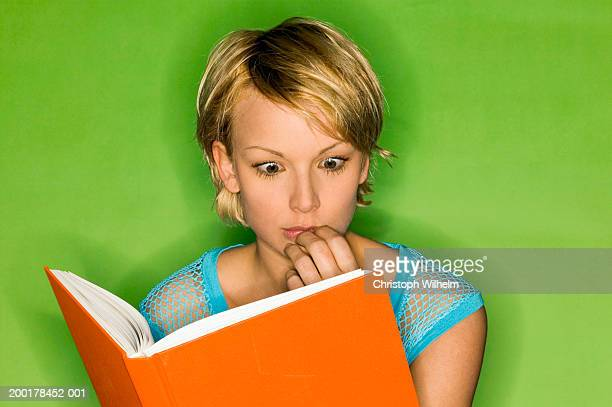 young woman with hand on mouth reading book, close-up - mesh shirt stock photos and pictures
