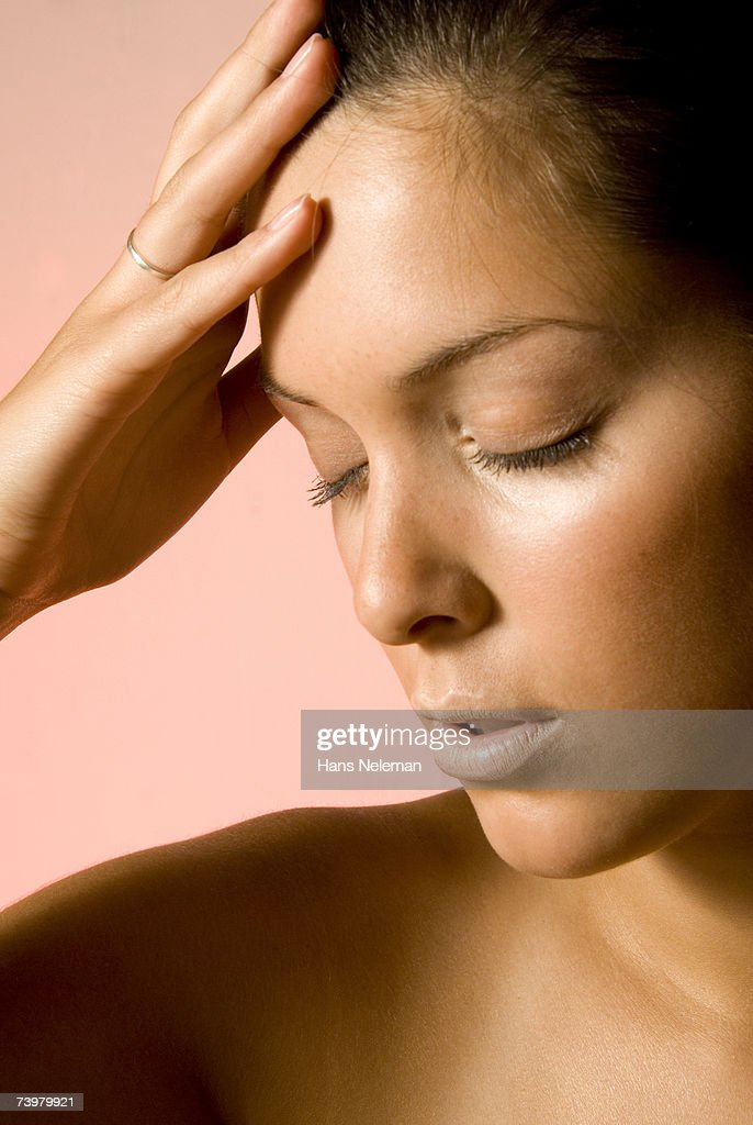 Young woman with hand to head, close-up : Foto de stock