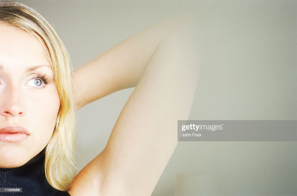 Young woman with hands behind head, close-up : Stock Photo