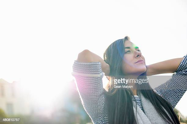 young woman with hands behind head in sunlight - geloof stockfoto's en -beelden