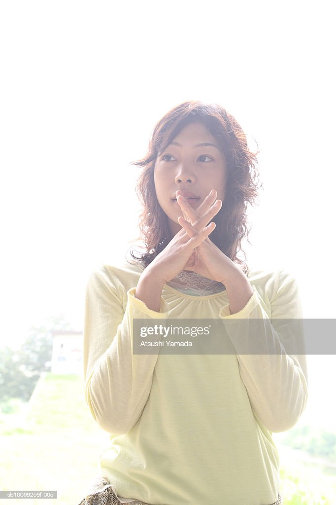 Young woman with hands clasped : Stockfoto