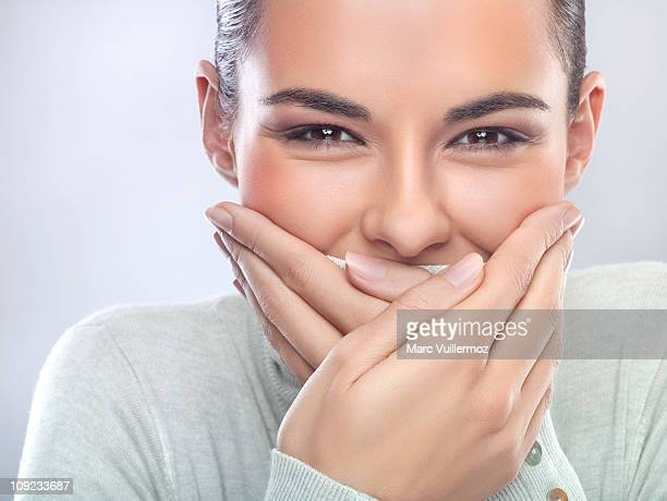 Young woman with hands covering mouth
