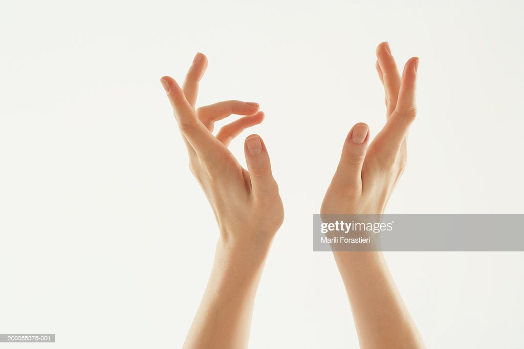 Young woman with hands in air, close-up : Stock Photo