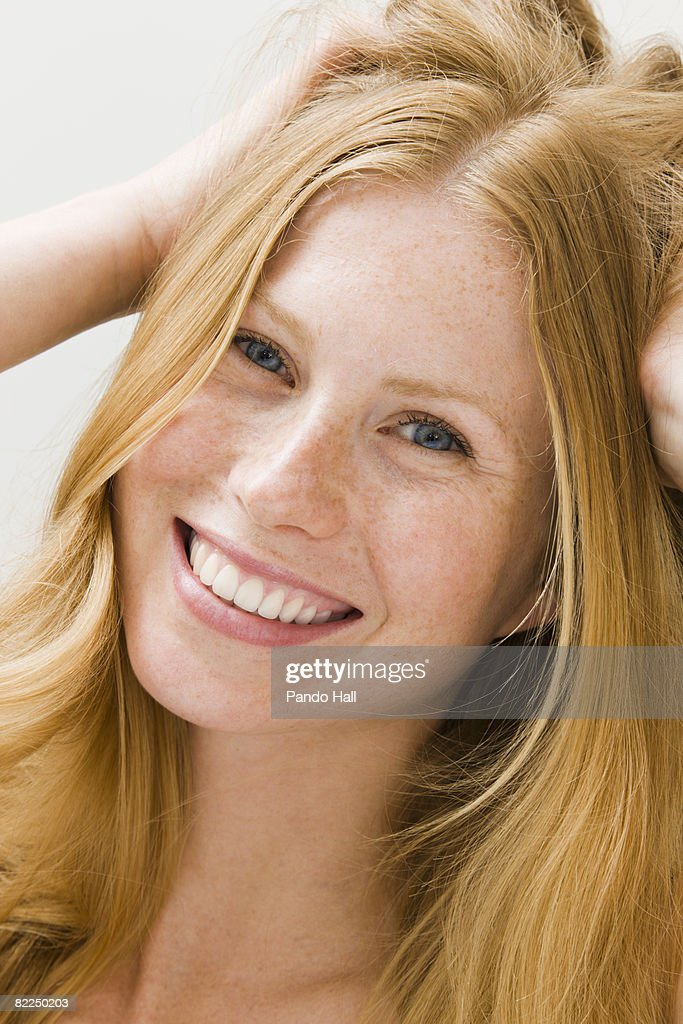 Young woman with hands in hair smiling : Stock Photo
