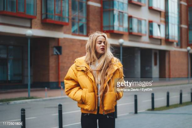 young woman with hands in pockets standing against building in city - hands in pockets stock pictures, royalty-free photos & images