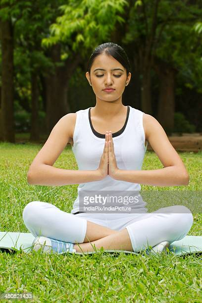 Young woman with hands in prayer position performing yoga at park
