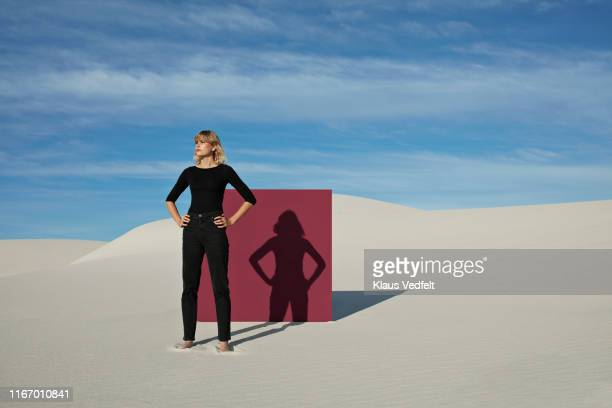 young woman with hands on hip standing against maroon portal at desert - hot female models stock pictures, royalty-free photos & images
