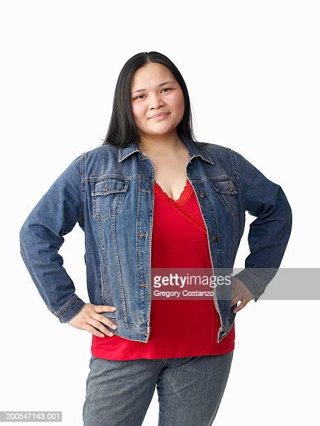 Young woman with hands on hips, on white background, portrait