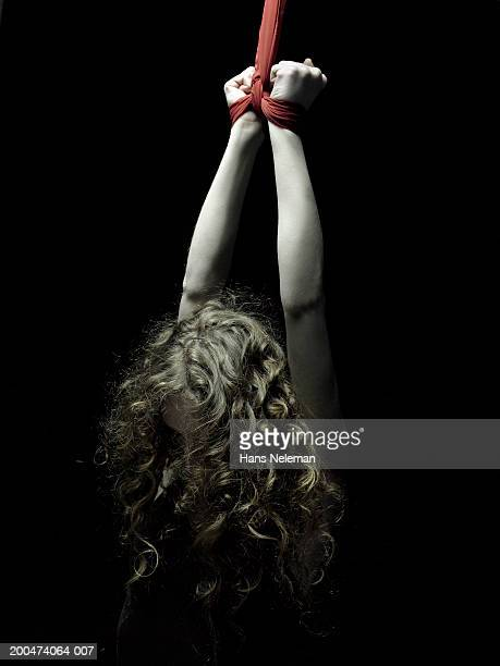 young woman with hands tied, arms pulled upwards, rear view - sadomasoquismo fotografías e imágenes de stock