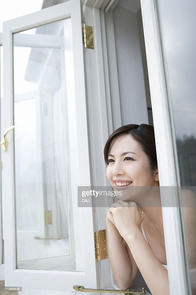 Young woman with hands under chin, looking out window,  side view  : Photo