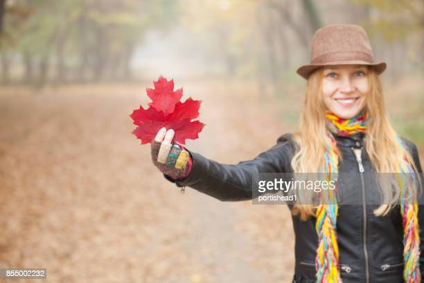 Young woman with hat holding red leaf