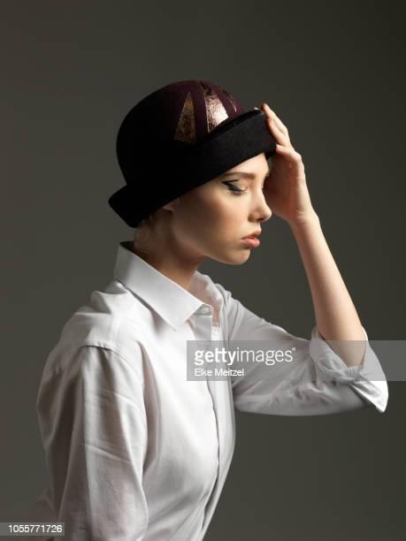young woman with hat in contemplation - kopfbedeckung stock-fotos und bilder
