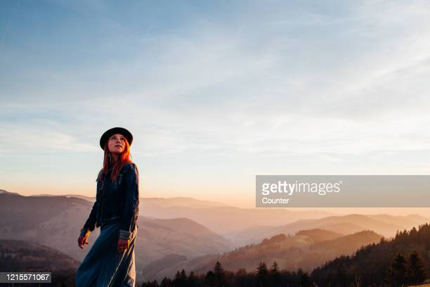 young woman with hat on mountain at sunset - baden württemberg stock-fotos und bilder