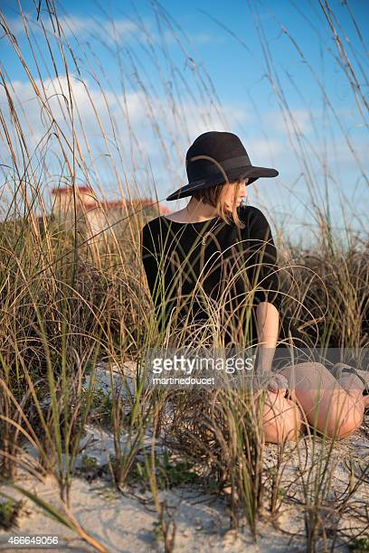 """young woman with hat sitting on the beach at sunset. - """"martine doucet"""" or martinedoucet stockfoto's en -beelden"""