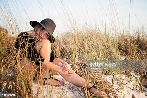 "young woman with hat sitting on the beach at sunset. - ""martine doucet"" or martinedoucet stockfoto's en -beelden"