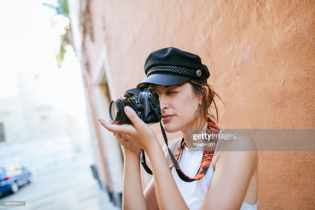 Young woman with hat taking a photo with a camera : Stock Photo