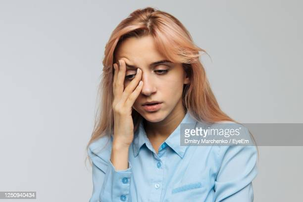 young woman with head in hands against white background - disappointment stock pictures, royalty-free photos & images